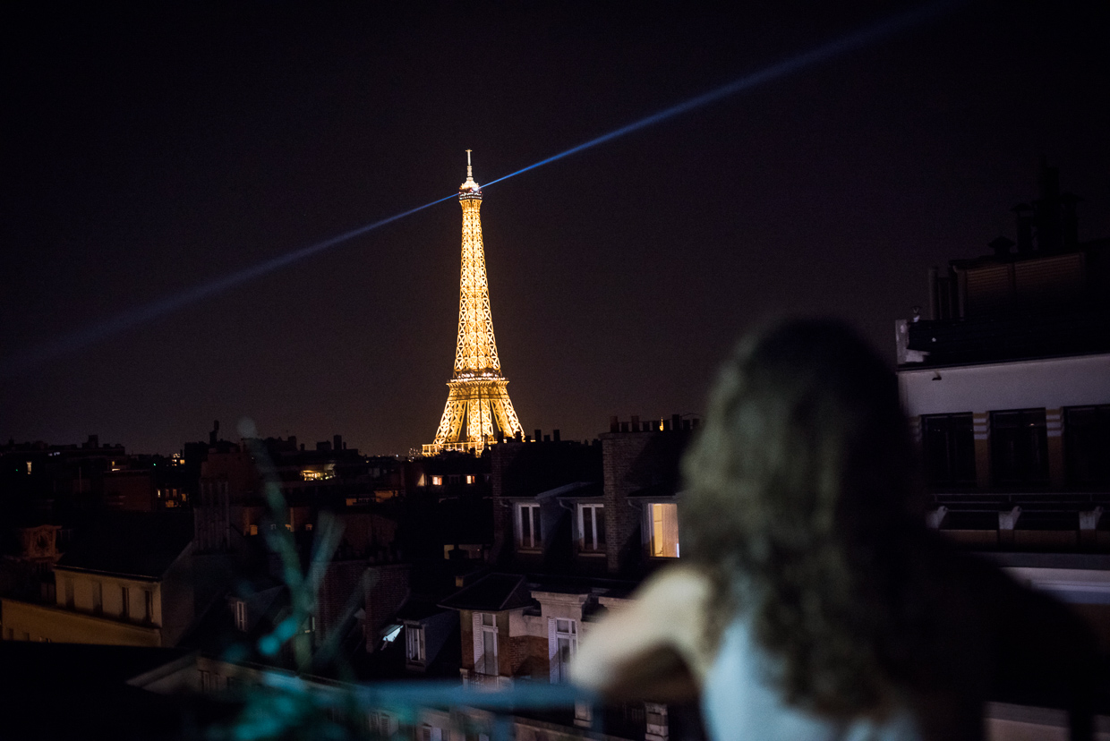 Genevieve McMahon looking at the illuminated Eiffel Tower at night