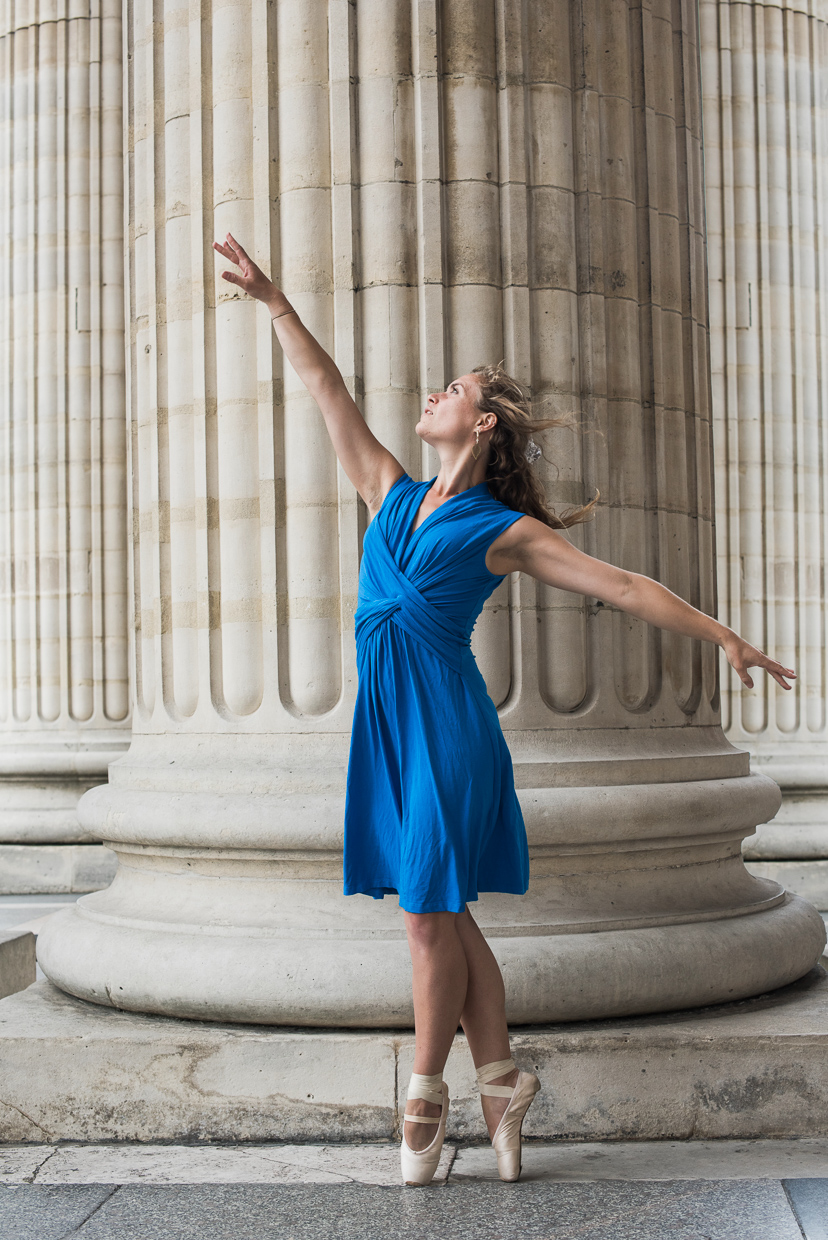 Lucy McMahon doing a ballet pose in front of a pillar in Paris