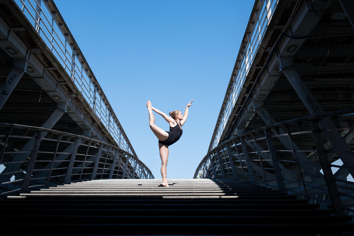 Lucy McMahon doing a ballet pose on a bridge in Paris
