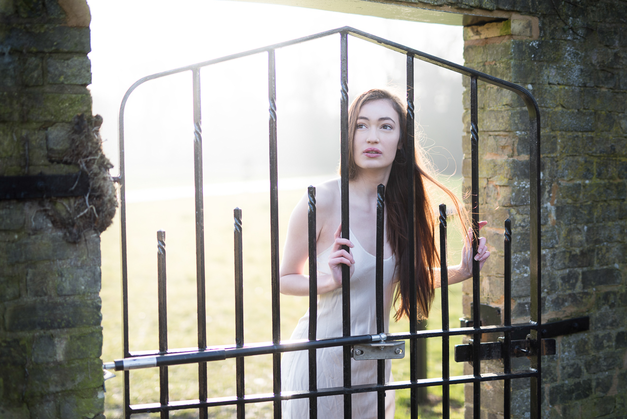 Emma Blacklay-Piech looking through a metal gate.